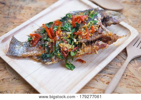 Thai style fish menu deep fried in chili sweet sauce on wood tray