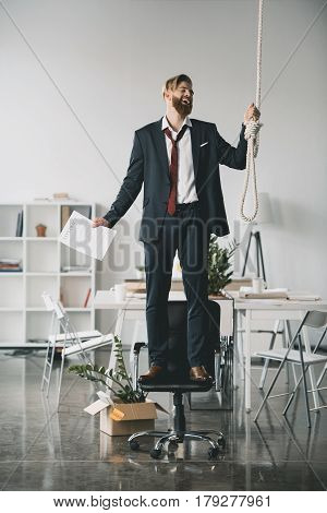 Depressed Young Fired Businessman Standing On Chair And Trying To Hang Himself