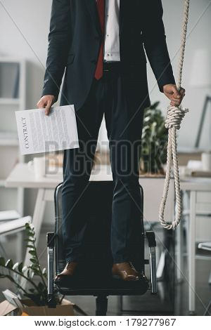 Cropped Shot Of Young Fired Businessman Standing On Chair And Trying To Hang Himself