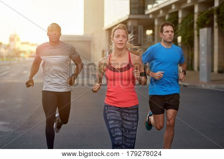 Diverse group of people exercising running jogging working out together in the city urban landscape, motion shot