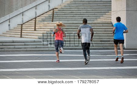 Multi racial group of people running exercising together, sprinting towards steps