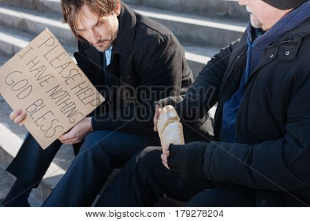 Share with you. Delighted elderly man sitting in semi position while looking at his companion in distress, breaking loaf of bread in two