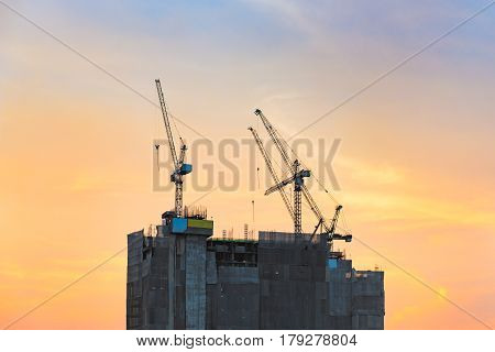 Industrial Construction Cranes At Construction Site With Sunset Sky Background