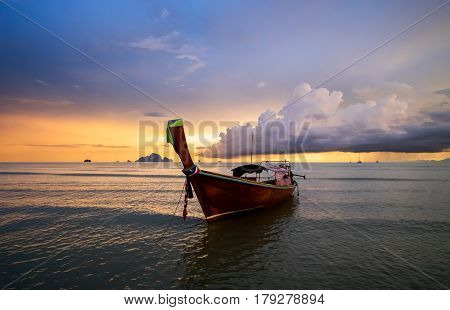 Traditional thai long tail boat on the sunset with colorful cloudy sky on backgraund. Andaman Sea Krabi Province of Thailand.