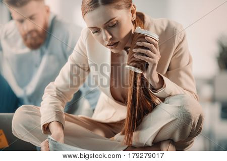 Attractive Young Businesswoman Holding Disposable Coffee Cup And Working With Documents