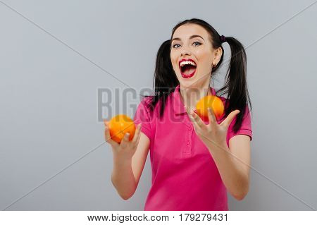 Woman with long straight hair, holding two oranges, looking up gray background.