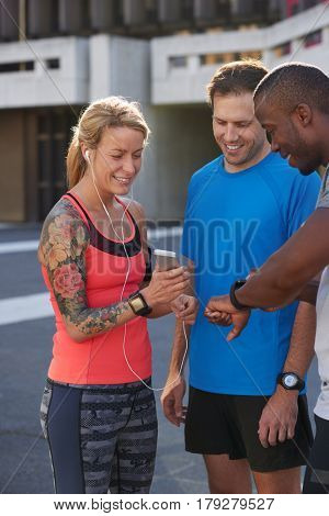 Sporty woman with tattoos shows her friends the new fitness app music playlist on her mobile phone wearable device technology