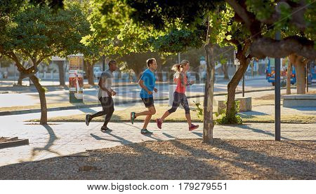 Urban running in the city, friends jogging exercising together between modern buildings and roads with sun flare