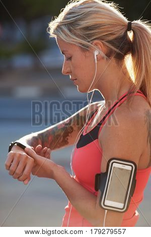Fit athletic woman with tattoos tracking her run exercise progress with wearable technology watch mobile smartphone in urban city