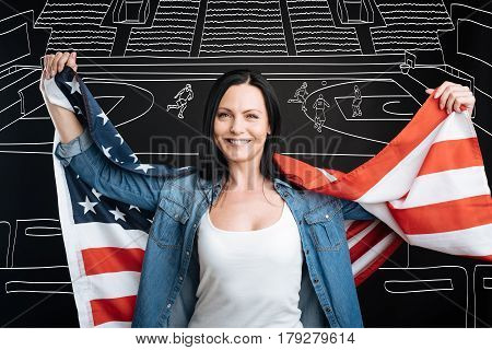 Basketball fan. Happy jubilant patriotic woman holding the American flag and smiling while supporting her favourite basketball team