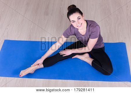 Sporty Woman Doing Stretching Exercises On The Floor