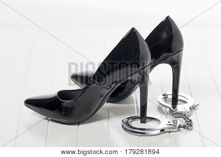 black high heels and hand cuffs on white
