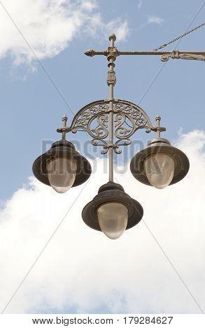hanging streetlamp against blue cloudy sky, closeup