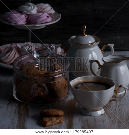 A Glass jar with cookies and a cup on a wooden table on dark background. Vintage Style.