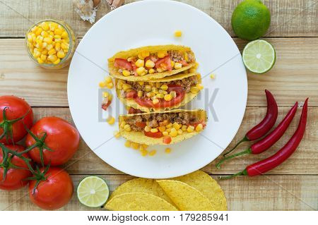Colorful mexican tacos cooked with crispy taco shells yellow corn red tomato and chicken mince