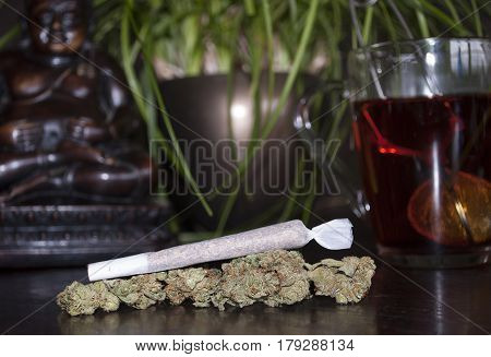 closeup of rolled marijuana weed joint and buds on wooden background with Buddha statuette and cup of rooibos tea