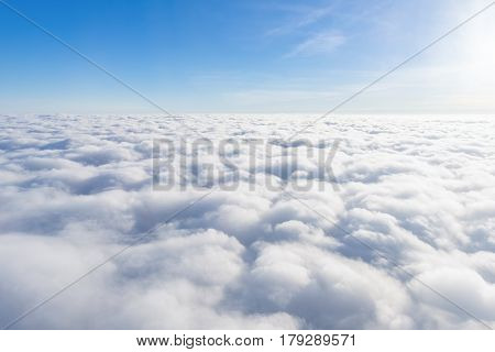View from airplane window above the clouds