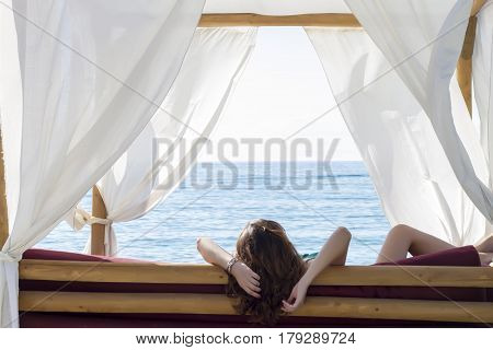 Rear View Of A Woman Sitting On Cozy White Lounger On The Beach. Soft Focus
