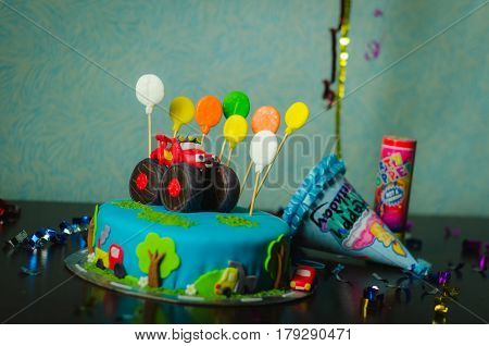 A closeup of a birthday cake decorated car and colorful ballons and presents.
