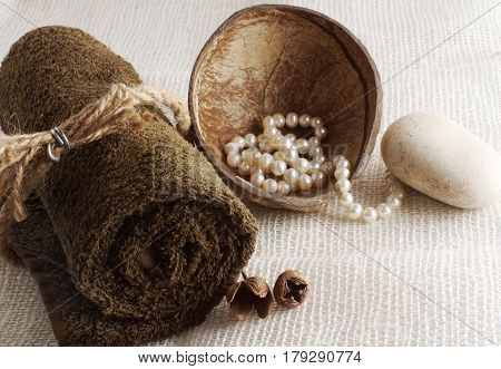 A rolled towel and pearls in a coconut on a light woven napkin preparation for a spa procedure