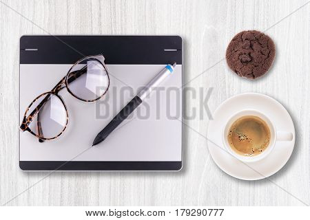 Top view of graphic tablet with pen and retro glass and espresso black coffee in coffee cup isolated on white background. For illustrators, photographer and designers tools concept
