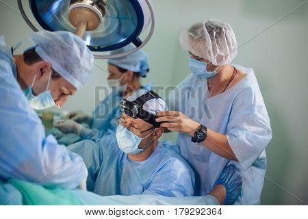 KIEV UKRAINE - JULY 24 2014 - Cameramn mounts GoPro on surgeon's head during the surgery on July 24 2016 in Kiev