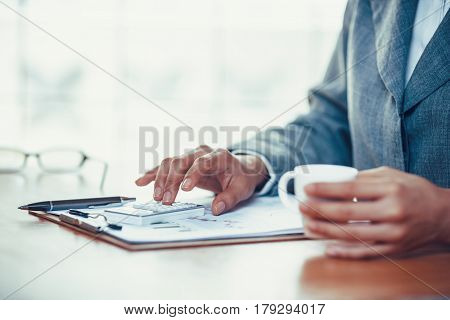 Businesswoman using calculator to analyze business chart