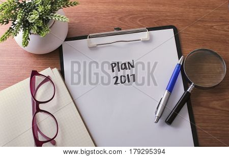 Plan 2017 Word On Paper With Glass Ballpen And Green Plant.