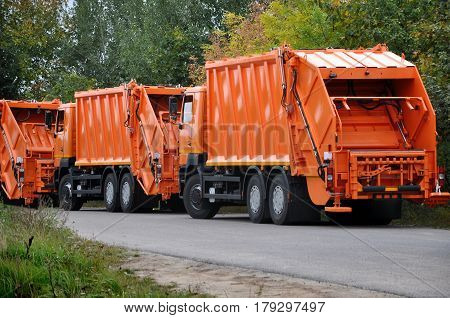 Grodno, Belarus - September 29, 2016: Many new orange garbage trucks on the road in perspective. Back view.
