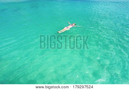 Woman floating and relaxing in turquoise waters at colorful tropical beach