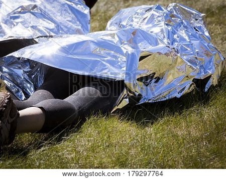 People wrapped in foil to keep warm laying on grass at the finish line after an endurance race.