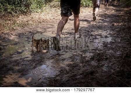 Close up of people running through water and mud puddle in an obstacle course race.