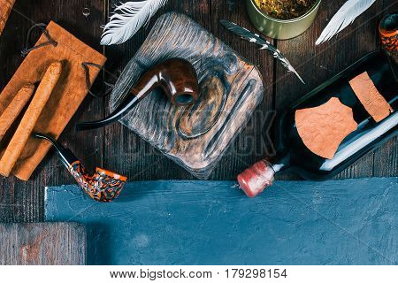 Frame of smoking pipes, cigars, tobacco and brandy bottles on dark wood desk and blackboard. Close up. Top view