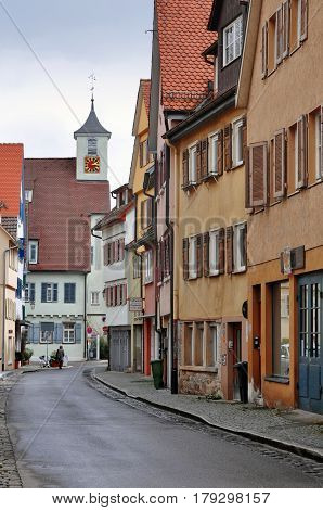 Tubingen, Germany - April 17, 2016: Old narrow street of Tubingen colored houses and tower of church. Baden-Wuerttemberg.