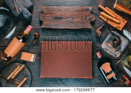 Frame of smoking pipes, cigars, tobacco and brandy bottles on dark wood desk. Western style. Wooden signboard as title. Top view