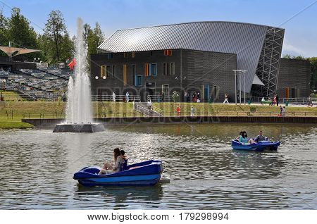 Molodechno, Belarus - July 3, 2014. Modern amphitheater in Molodechno, Belarus. Lake with catamarans and visitors in the foreground.