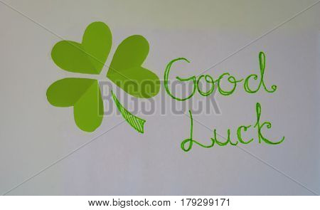 On a white background lined with three green heart shaped shamrock green felt-tip pen and written good luck as the background for a card or greetings.