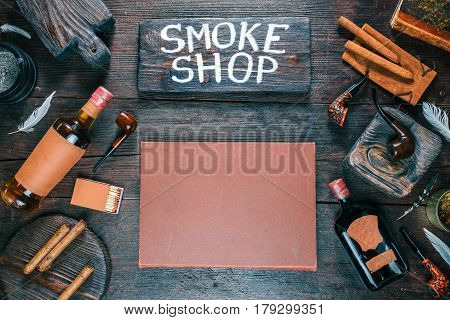 Frame of smoking pipes, cigars, tobacco and brandy bottles on dark wood desk. Western style. Wooden signboard with text 'Smoke shop'. Top view