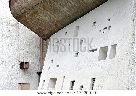 RONCHAMP, FRANCE - APRIL 23, 2016: Pilgrimage Church of Notre Dame du Haut in Ronchamp.White facade with different windows. The architect is Le Corbusier. Franche-Comte, France.