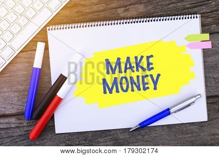 Notebook With Make Money Handwritten On Wooden Background And Modern Computer Keyboard. Top View Com