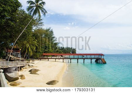 Relax on a deserted beach in an island of Tropical paradise. Pier on the beach at Pulau Perhentian Malaysia.