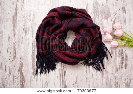 Fashion concept. Red and blue scarf and pink tulips. Top view light wood background