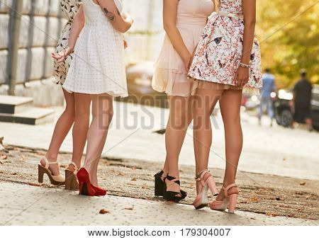girls women friends with sexy legs standing. outdoor street city