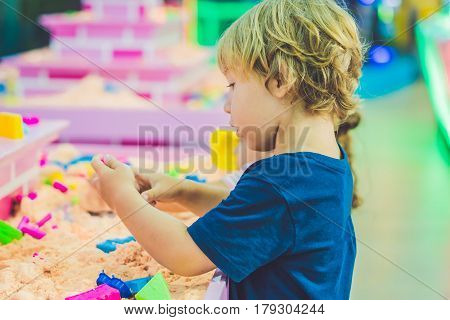 Boy Playing With Kinetic Sand In Preschool. The Development Of Fine Motor Concept. Creativity Game C