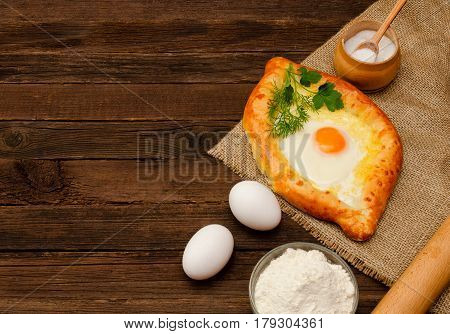 Khachapuri with eggs on sackcloth salt flour and eggs. Georgian cuisine. Space for text