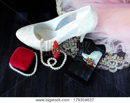 White women's shoes with high heels, red lipstick and smartphone with the photo in the screen. Fashion concept. Glamorous composition for a wedding, a prom and a date