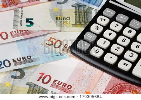 One black calculator on Euro banknotes in various denomination.