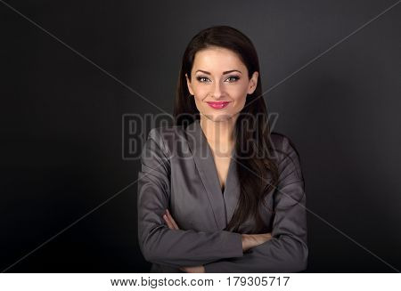 Beautiful Smiling Business Woman In Grey Suit Looking Happy With Folded Arms On Dark Background With