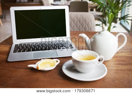 Close-up of a laptop computer with blank screen and cup of green tea with lemon on a wooden table to start working morning in urban life. Browsing Internet while drinking tea and relaxing