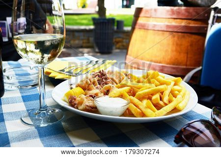 Calamari and fries on laid table in a restaurant
